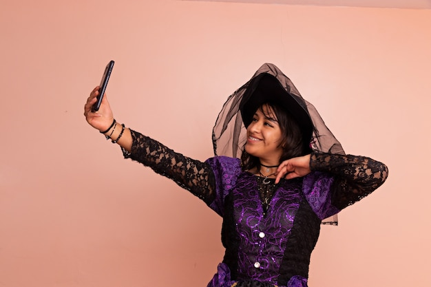 魔女の衣装を着た若い女性が、無地の背景で自分撮りをポーズして写真を撮る