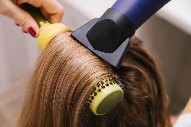 Молодая женщина сушит волосы феном. девушка расчесывает волосы. профессиональные средства по уходу за волосами. салон красоты.
