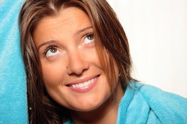 青いタオルで髪を乾かす若い女性