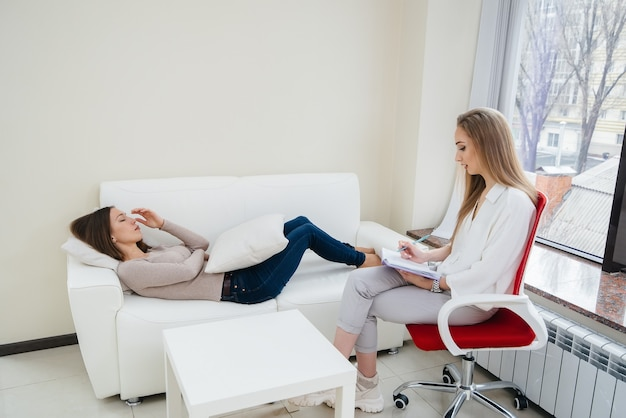 Молодая женщина во время депрессии общается с психологом в офисе