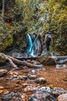 ヨホアのセロアズールメーンバル国立公園(パナカム)の自然の滝を楽しむ若い女性。ホンジュラス