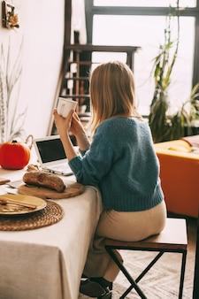 若い女性は朝のコーヒーを楽しんで、彼女のラップトップで働いています