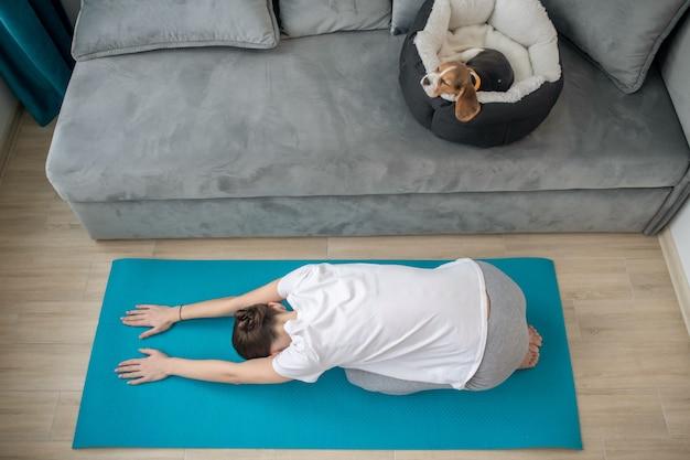 犬の場所で眠っている子犬が家で運動している若い女性