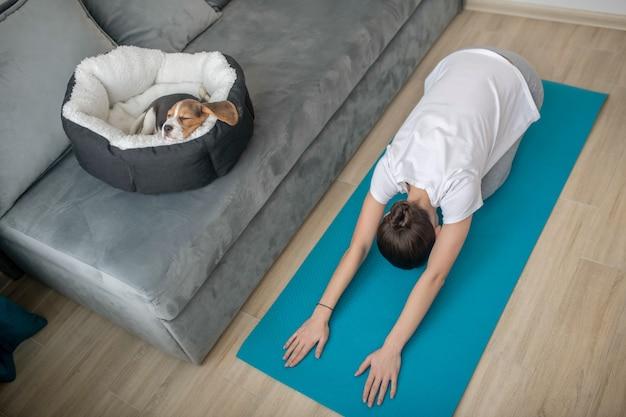 Молодая женщина тренируется дома, пока ее щенок спит в месте для собак