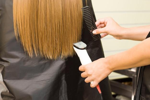 Молодая женщина стригется машинкой для стрижки. парикмахерская.