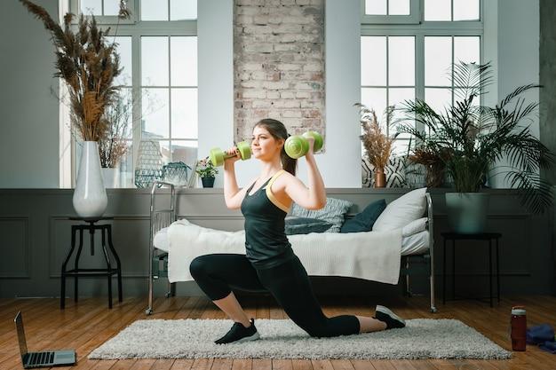若い女性が自宅でスポーツに出かけ、ノートパソコンからオンラインでトレーニングする