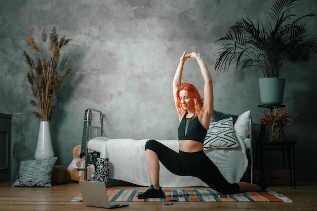젊은 여성이 집에서 스포츠, 온라인 운동에 들어갑니다.