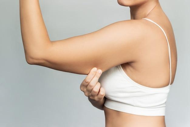 과도한 지방이 있는 팔뚝의 피부를 잡고 있는 젊은 여성이 느슨하고 처진 근육을 꼬집고 있습니다.