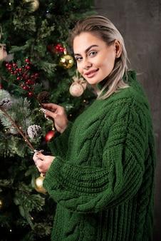 若い女性がモミの木の枝にクリスマスツリーのおもちゃを掛ける