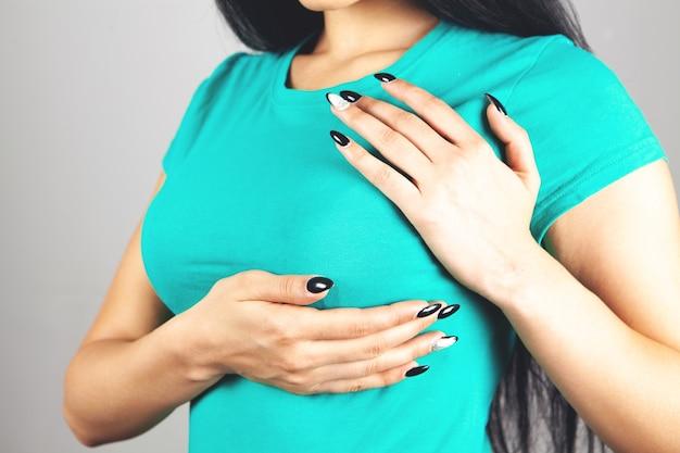 회색 배경에 가슴 통증이 있는 젊은 여성