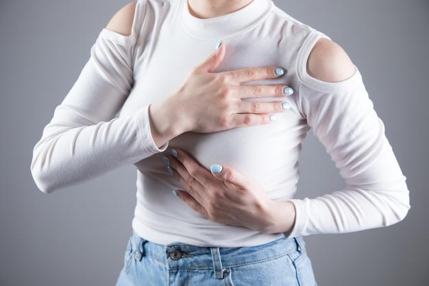 젊은 여성이 회색 장면에 가슴 통증이 있습니다.