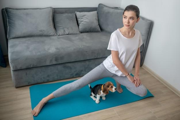 Молодая женщина тренируется, пока ее щенок сидит рядом с ней