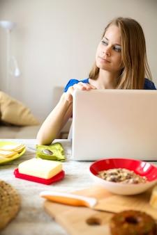 ラップトップコンピューターを使用しながら朝食をとっている若い女性。