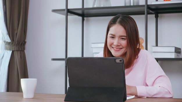 自宅のタブレットコンピューターで家族とビデオ通話をしている若い女性。