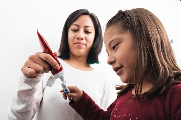 어린 소녀가 욕실에 있는 칫솔에 치약을 넣는 것을 돕는 젊은 여성