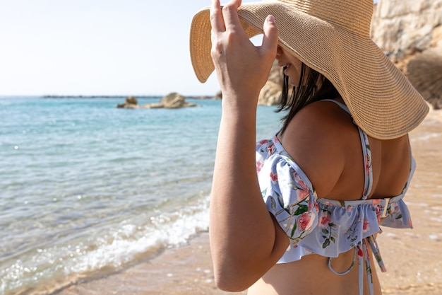 若い女性が海岸の大きな帽子の下で太陽から顔を隠します。