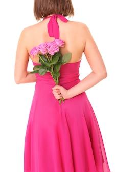 흰색 위에 그녀의 뒤에 핑크 장미 다발을 숨기는 젊은 여자