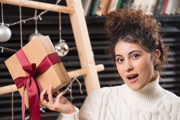 활과 선물 상자를 들고 젊은 여자