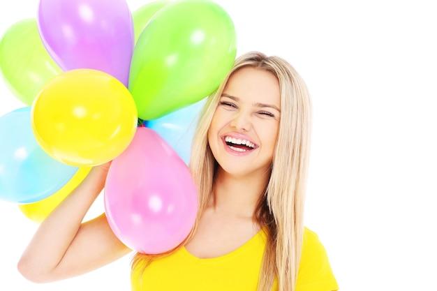 흰색 배경 위에 baloons를 들고 젊은 여자
