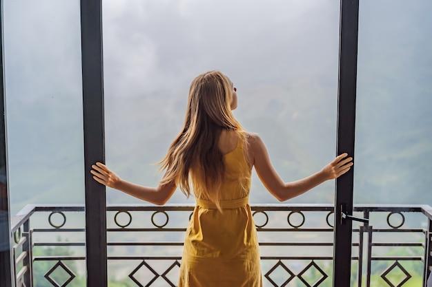 Молодая женщина держит чашку кофе, сидя на стуле на балконе, глядя на горы и зелень