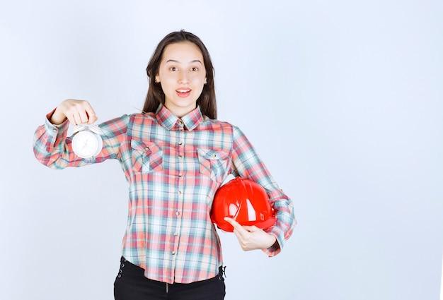 クラッシュヘルメットと目覚まし時計を持っている若い女性。 無料写真