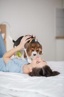 Молодая женщина держит своего маленького симпатичного щенка и чувствует себя мирно