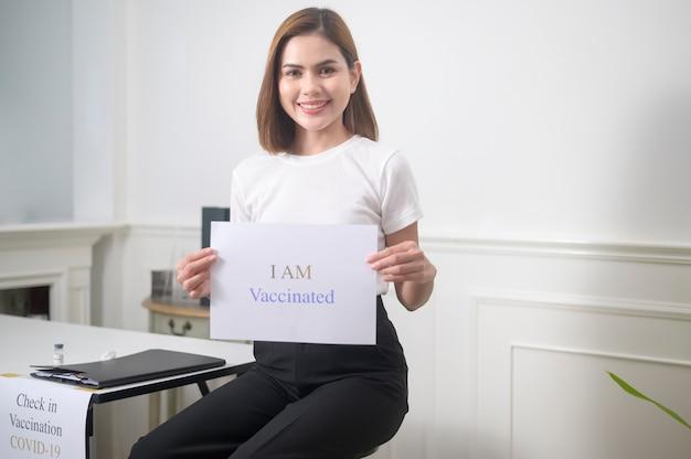 나는 예방 접종 사인, covid-19 예방 접종 및 건강 관리 개념을 들고있는 젊은 여성