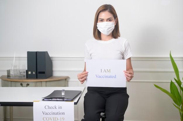 나는 예방 접종 표지판, covid-19 예방 접종 및 건강 관리 개념을 들고 있는 젊은 여성