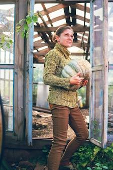 Молодая женщина держит в руках тыкву