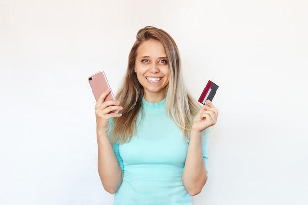 온라인 구매 비용을 지불하기 위해 플라스틱 신용 카드와 휴대폰을 손에 들고 있는 젊은 여성