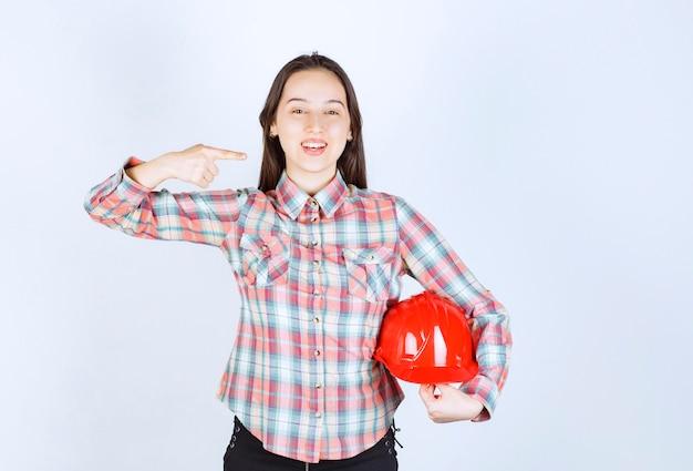 Молодая женщина держит красный защитный шлем и показывает пальцем в сторону.