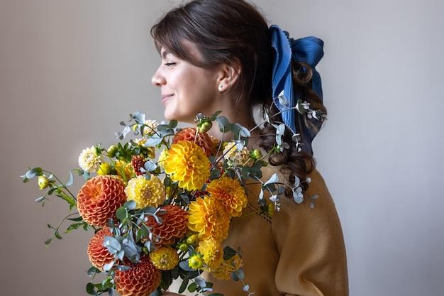 Молодая женщина держит букет цветов хризантем