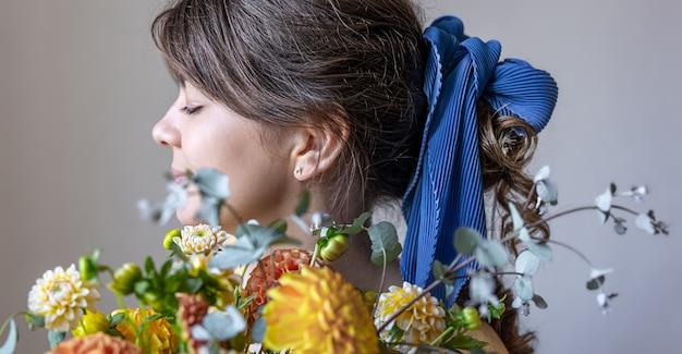 Молодая женщина держит букет хризантем