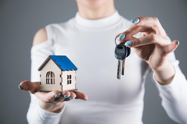젊은 여자는 회색 벽에 그녀의 손에 집과 키를 보유