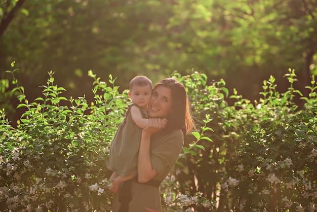 젊은 여자는 그녀의 팔에 작은 아기를 안고 있습니다. 아름다운 어머니가 재스민 덤불 근처의 녹색 공원에서 딸과 함께 산책