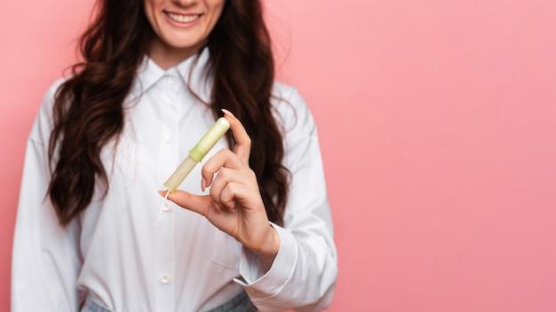 若い女性は、使いやすいようにアプリケーターを手に持った月経スワブを持っています。ピンクの背景。テキスト用のスペース。女性の衛生の概念。