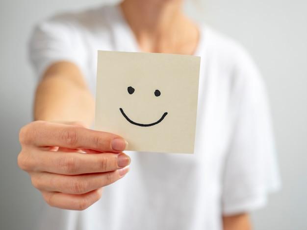 Молодая женщина держит в протянутой руке бумажный стикер с нарисованным смайликом. сосредоточьтесь на руке и наклейке, размытый фон