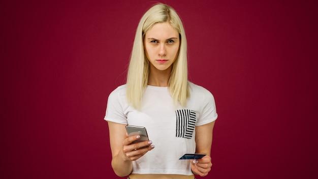젊은 여성이 그녀의 손에 스마트 폰과 신용 카드를 보유하고 있습니다. 차단 또는 잘못 입력 된 비밀번호로 인한 은행 카드 문제. 고객 지원과의 커뮤니케이션