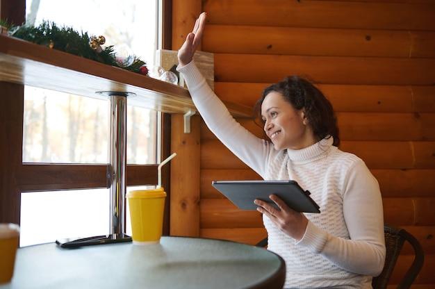 Молодая женщина держит планшет и машет рукой через окно, сидя за столиком уютного деревянного кафе