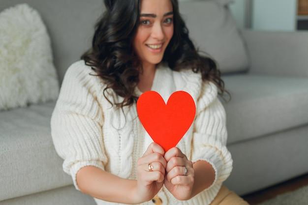 젊은 여자는 심장의 형태로 발렌타인 카드를 보유하고 있습니다. 휴가. 발렌타인 데이.