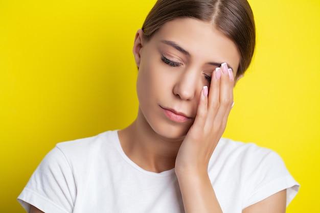 한 젊은 여성이 머리 가까이에 손을 대고 심한 두통을 느낍니다.
