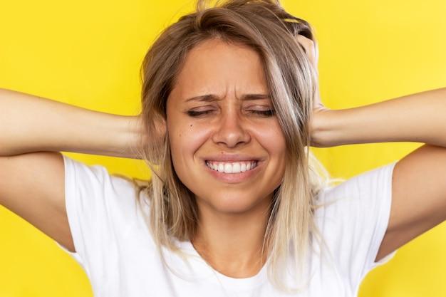 若い女性は彼女の頭を保持し、色の黄色の背景の頭痛で彼女の耳を覆います