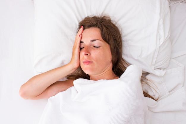 Молодая женщина держит голову и лежит в постели. концепция бессонница, головная боль, недомогание, болезни. плоская планировка, вид сверху