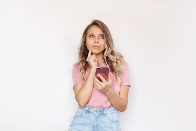 한 젊은 여성이 손에 휴대전화를 들고 문자를 위한 빈 카피 공간을 올려다보며 생각합니다