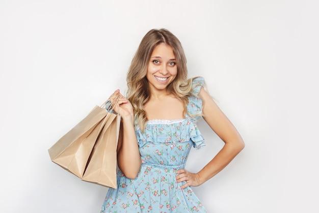Молодая женщина держит в руке бумажные эко-пакеты, изолированные на белом фоне покупки и мода