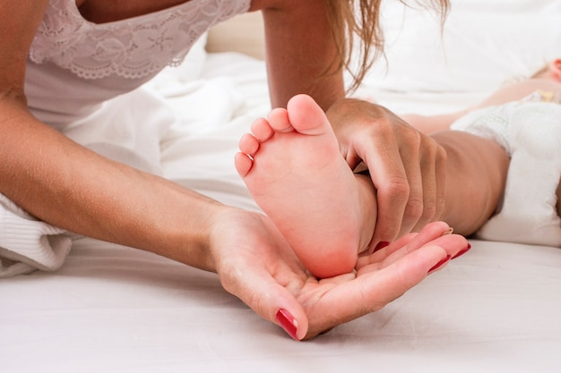 若い女性がベッドで眠っている赤ちゃんの足を保持しています。コンセプト母親の愛とケア