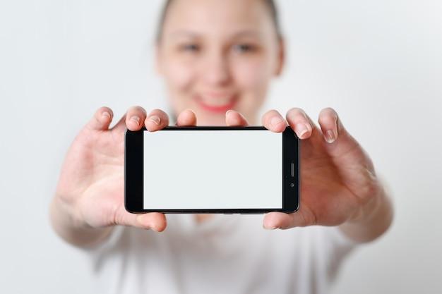 若い女性はcopyspaceのための場所と白い画面で電話を水平に保持しています。