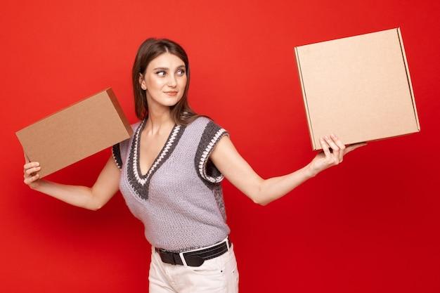 Молодая женщина держит две картонные коробки на красной стене