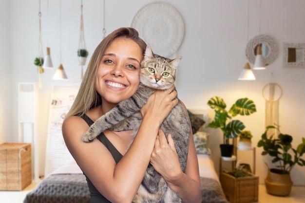 Молодая женщина держит в руках молодого полосатого кота на фоне уютной комнаты гармония и уют
