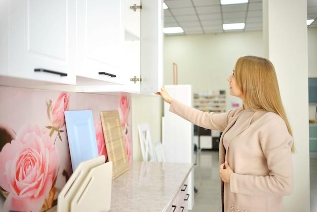 Молодая домохозяйка выбирает кухонный гарнитур для дома. концепция улучшения дома.